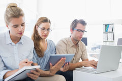 Concentrated three young people in office Stock Image
