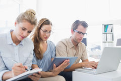 Concentrated three young people in office Stock Photos