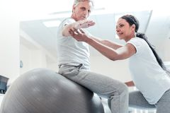 Concentrated trainer helping old man exercise. Very good. Determined old wrinkled grey-haired men sitting on a ball for exercises and a pretty young dark-haired Stock Images