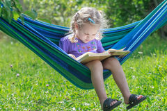 Concentrated two years old girl reading opened book on hanging hammock in green summer garden outdoors royalty free stock photography