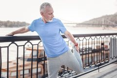 Concentrated unshaken man standing and stretching his leg. Warm up firstly. Concentrated unshaken strong man standing on the quay holding by the railings and Royalty Free Stock Images