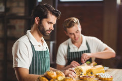 Concentrated waiters tidying up the pastries Royalty Free Stock Image