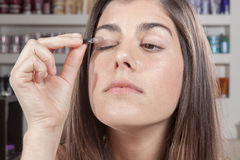 Concentrated woman applying eye shadow itself Stock Photos