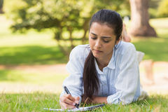 Concentrated woman with book and pen in park Royalty Free Stock Photos