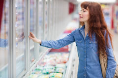 Concentrated woman buying frozen food. In supermarket stock images