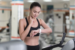Concentrated woman controlling her pulse after training. Be healthy. Concentrated young slim woman controlling her pulse by using smart watch after having Royalty Free Stock Photography