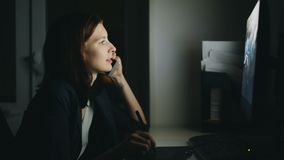 Concentrated woman designer talking phone working in office at night using computer and graphics tablet to finish job