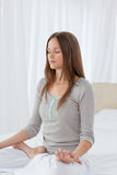 Concentrated woman doing yoga exercises on the bed Royalty Free Stock Images