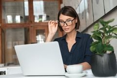 Concentrated woman in eyeglasses working with laptop computer. By the table in co working office Royalty Free Stock Image