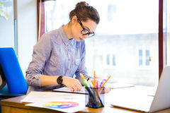 Concentrated woman fashion designer drawing sketches in office Royalty Free Stock Image