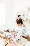 Concentrated woman fashion illustrator drawing. Image of young concentrated woman fashion illustrator sitting at the table and drawing. Looking aside stock images