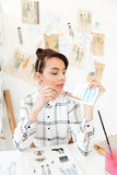 Concentrated woman fashion illustrator sitting at the table. Image of young concentrated woman fashion illustrator sitting at the table. Looking aside Royalty Free Stock Photo