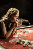 Concentrated woman holding drink while playing poker Royalty Free Stock Images