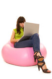 Concentrated woman with laptop. Sitting on pink chair Royalty Free Stock Photo
