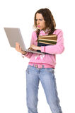 Concentrated woman with laptop and pile of books Royalty Free Stock Images