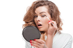 Concentrated woman looking at mirror while putting eyeliner. Isolated on white Stock Photography