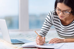 Concentrated woman making notes at home Stock Photo