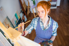Concentrated woman painter holding art palette and painting on canvas. Portrait of concentrated beautiful young woman painter holding art palette and painting on royalty free stock photo