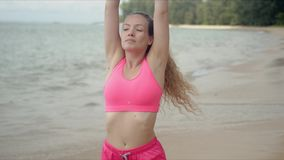 Concentrated woman in pink sportswear stretching raised hands on beach stock footage