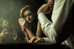 Concentrated woman playing poker with cards in hands Stock Photography