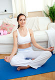 Concentrated woman practicing yoga at home Stock Photos