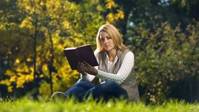 Concentrated woman reading scientific book in autumn park, sitting on grass royalty free stock photos