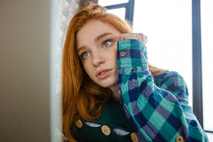 Concentrated woman with red hair hugging knitted cushion. Closeup of concentrated pencive young woman with long red hair in plaid shirt hugging knitted cushion stock photos