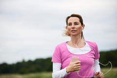 Concentrated woman running through the fields. Concentrated woman listening to music running through field, copy space to the left Stock Image