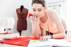 Concentrated woman seamstress using pattern and drawing on red fabric Royalty Free Stock Image