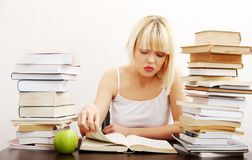 Concentrated woman sitting with stack of books Royalty Free Stock Images