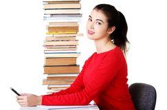 Concentrated woman sitting with stack of books Stock Images