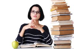 Concentrated woman sitting with stack of books.  Stock Photo