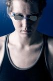Concentrated woman swimmer. Portrait of a looking downwards concentrated woman swimmer, blue toned on blue background Stock Photo