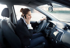 Concentrated woman talking by phone and driving car Royalty Free Stock Images