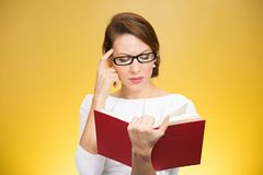 Concentrated woman thinking on book content. Young elegant woman in eyeglasses having problems with understanding while reading book isolated on yellow stock images