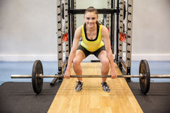 Concentrated woman about to lift a barbell and weights Stock Image