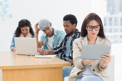 Concentrated woman using digital tablet with colleagues behind in office Stock Photo