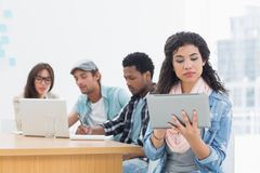 Concentrated woman using digital tablet with colleagues behind in office Royalty Free Stock Photos