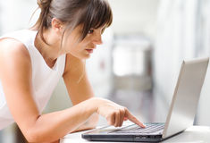 Concentrated woman working at laptop Royalty Free Stock Photography