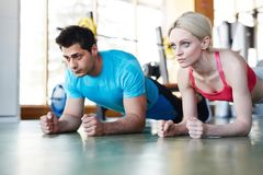 Serious sportive man and woman doing abs exercise stock photo
