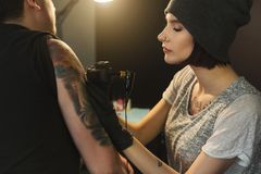 Young woman tattooist doing tattoo on shoulder. Concentrated women tattooist doing tattoo with tattoo machine on male shoulder. Unusual female profession, copy Royalty Free Stock Photography