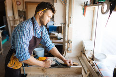 Concentrated woodworker in workshop Royalty Free Stock Photo