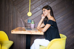 Confident young woman in smart casual wear working on laptop while sitting near window in creative office or cafe Royalty Free Stock Image