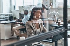 Concentrated at work. Modern young woman using computer while wo Royalty Free Stock Photo