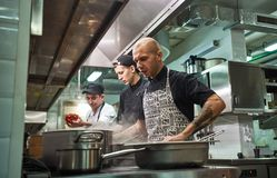 Concentrated at work. Professional team of chef and two young assistants cooking in a restaurant kitchen. Food preparation concept stock photography