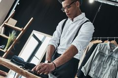Concentrated on work. Serious young man arranging menswear while. Standing in the showroom Stock Photos