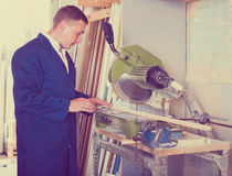 Concentrated workman cutting wooden planks using circular saw Royalty Free Stock Photos