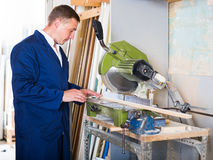 Concentrated workman cutting wooden planks using circular saw. In workshop Stock Images