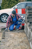 Concentrated workman laying paving bricks in winter Stock Image
