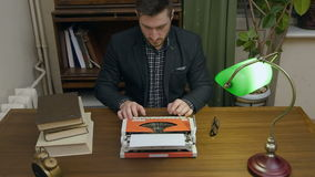 Concentrated writer typing new book on a red vintage typewriter in his cabinet stock video